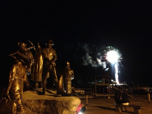 Life-sized sculptures on Dave Rubin's The Rock appear to be watching the fireworks show late on the Fourth of July.