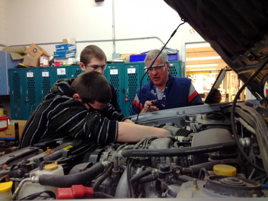 Jacob Alvey, Joe Harris, and David Sweetman look under the hood of a car in the auto shop.