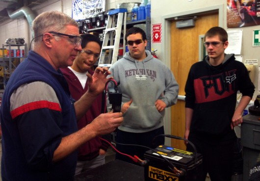 David Sweetman, Jeasten Correa, and Daniel Guthrie in the Kayhi auto shop.