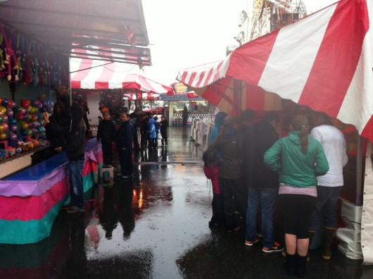 Fair attendees cluster under awnings to keep out of the rain Thursday.