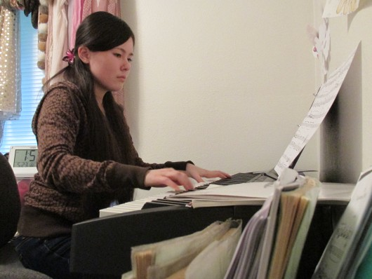 Hana Oshima practices piano in her room.