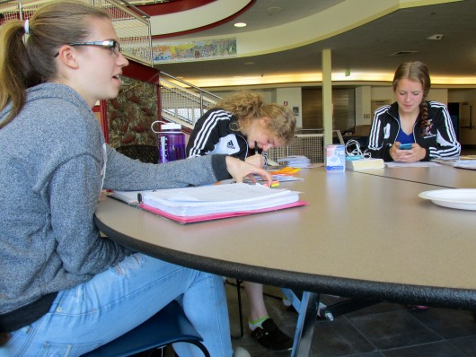 Natasha Bolshakoff, Tabitha Gordanier, and Katie Powers work on homework at Sitka High School. Because they often miss school to travel for games, the team has gotten used to doing their homework on road.