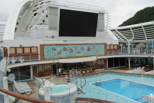 A pool with a movie screen hovering above it on the Crown Princess.