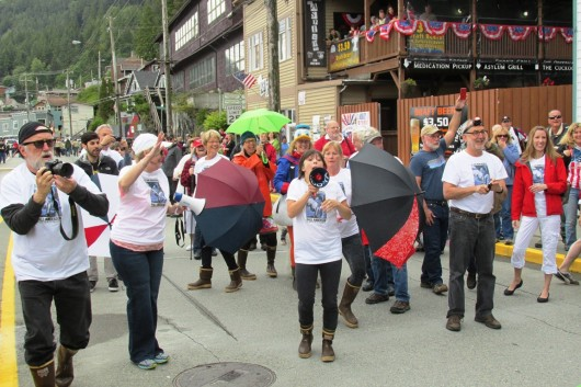 "A flash mob halted Ketchikan's Fourth of July parade briefly, as friends and fans of retiring news photographer Hall Anderson, wearing T-shirts printed with his photo, danced and ""flashed"" cameras at Anderson, the parade grand marshal."