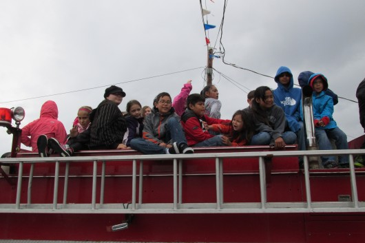 Children sit on top of a fire truck in the parade.
