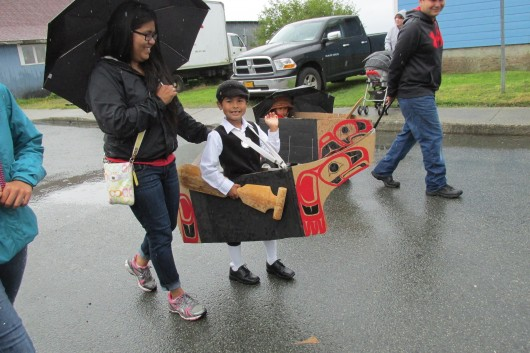 A boy dressed as a Tsimshian pioneer in a canoe.