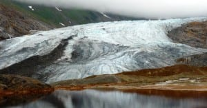 A glacier reflects in a naturally occurring pool of rusty, acidic water at the site of one of the KSM Prospect's planned open-pit mines. The British Columbia project, northeast of Ketchikan, is drilling for higher-value ore this summer. (Photo by Ed Schoenfeld/CoastAlaska News)