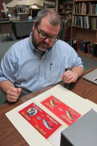 Researcher Ross Coen views some of the labels in the museum's collection.