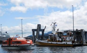 A cruise-ship lightering boat passes a salvage tugboat docked at Ketchikan's Berth 3, which was extensively damaged by the cruise ship Infinity on Friday. (Photo by Ed Schoenfeld/CoastAlaska News)