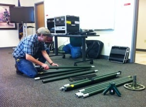 Kevin Hurtley assembles part of the portable transmission tower for the new emergency broadcast studio.