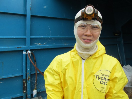 Cat wears a Tyvek suit while cleaning out a fuel tank on a crab boat.