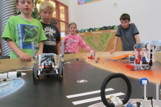 Campers watch as one team's EV3 robot rolls toward its mission.