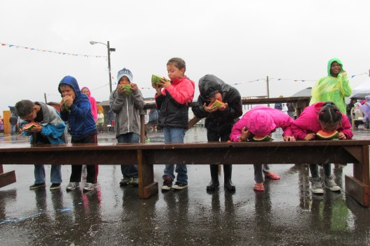 Kids participate in a watermelon eating contest.