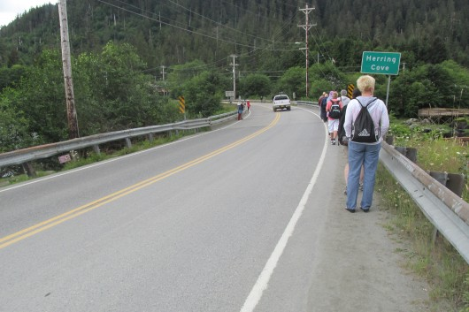 Tourists walk onto the shoulder of the bridge at Herring Cove.