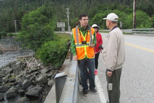 Tourism compliance agent Marco Torres answers tourists' questions on the shoulder of the bridge.
