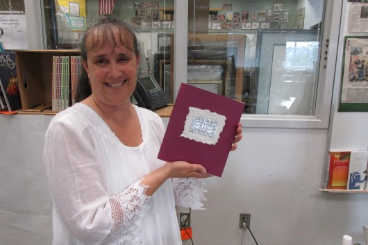 Penny Ranniger, a librarian at Houghtaling, shows a journal she made at the Basic Arts Institute.
