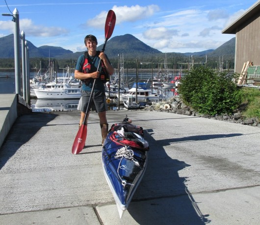 Zachary Brown stands with his kayak at Bar Harbor before continuing his journey home to Gustavus.