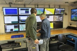 Capt. Adam Seamans and Steve Roberts stand in front of a wall of computer screens on board the ocean research vessel Sikuliaq.