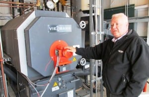 Airport Manager Mike Carney stands next to the Ketchikan International Airport's new biomass wood-pellet boiler. (Photo by Leila Kheiry)