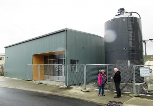 Karen Petersen and Mike Carney talk outside the Ketchikan International Airport's new biomass boiler building. The pellet silo on the right holds up to 30 tons. (Photo by Leila Kheiry)