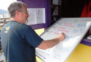 Lions Club volunteer Glenn Brown changes the leader whiteboard at the Bar Harbor weigh-in station Sunday afternoon.  (Ed Schoenfeld/CoastAlaska News)