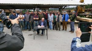 Gov. Bill Walker signs SB32 into law at Viking Lumber in Klawock, on Prince of Wales Island. (Photo courtesy Jan Trojan)